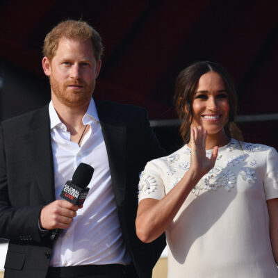 Prince Harry in a black suit on stage with Meghan Markle in a white dress