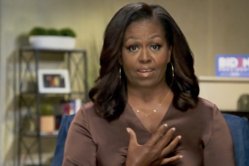 Michelle Obama with her hand over her heart in a brown blouse