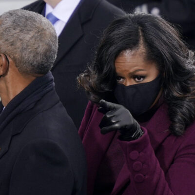 Barack Obama next to a pointing Michelle Obama