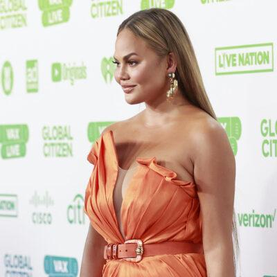Chrissy Teigen in an orange dress