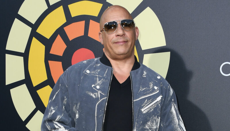Vin Diesel smiling in a blue jacket with black sunglasses