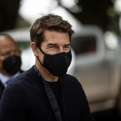 Tom Cruise in a black mask and sweater outdoors