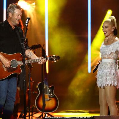 Gwen Stefani in a white dress on stage with Blake Shelton