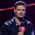 Ryan Seacrest in a black shirt holding a microphone