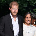 Prince Harry in a black suit with Meghan Markle in a white dress