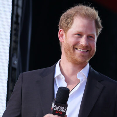 Prince Harry smiling in a black suit holding a microphone