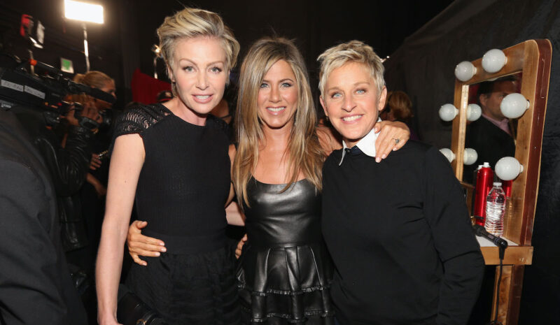 Portia de Rossi, Jennifer Aniston, and Ellen Degeneres smiling with each other in black outfits