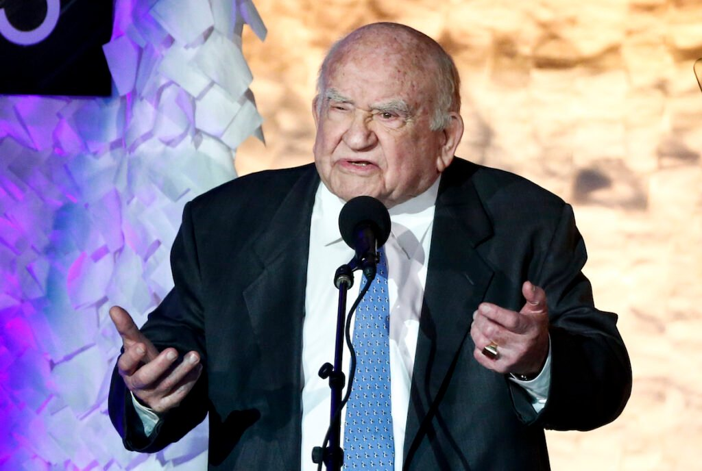 Ed Asner in a suit making a joke on stage in 2016