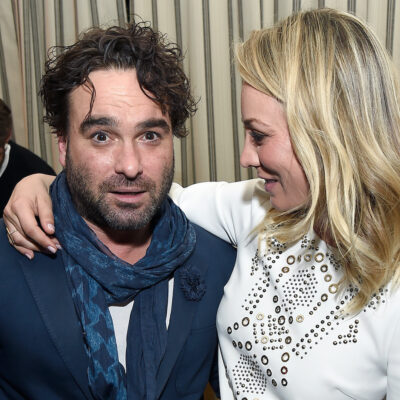 Kaley Cuoco in a white dress eyeing Johnny Galecki in a blue suit