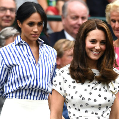 Meghan Markle in a blue and white outfit following Kate Middleton in a white dress