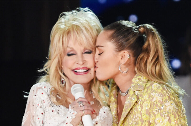miley cyrus kissing dolly parton on the cheek during a performance
