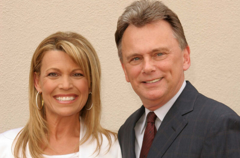 Vanna White on the left, standing with Pat Sajak at a charity event.