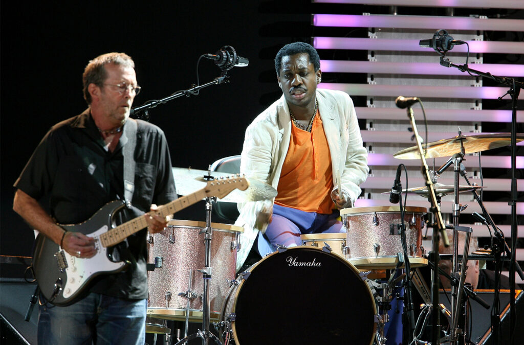 Steve Jordan playing drums on stage with Eric Clapton.