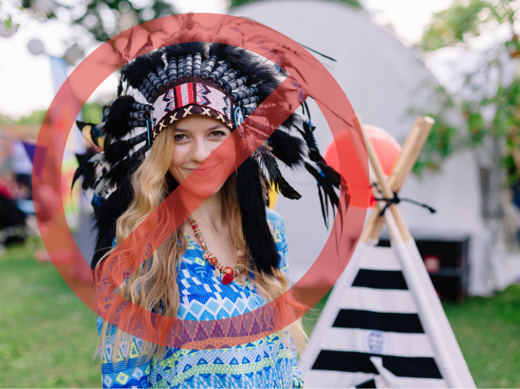 A white person disrespectfully wears a ceremonial head dress