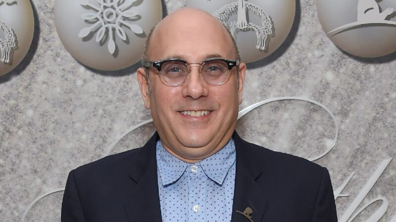 Willie Garson wears a blue shirt and dark suit jacket against a gray background