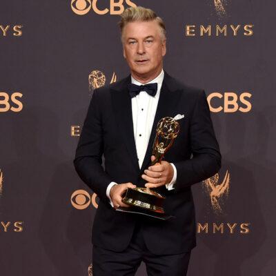 Alec Baldwin holding an Emmy award.