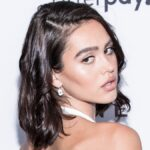 Amelia Hamlin wears a white dress and looks over her shoulder on the red carpet