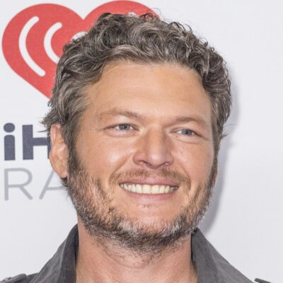 Blake Shelton wears a gray button down shirt on the red carpet
