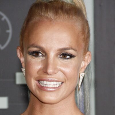 Britney Spears wears a gold dress and smiles big for the camera on the red carpet