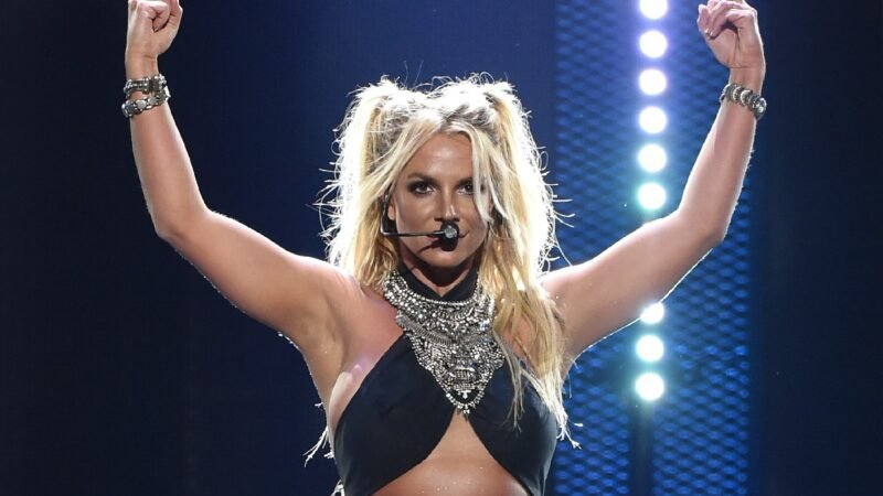 Britney Spears wears a black top and raises her arms above her head on stage