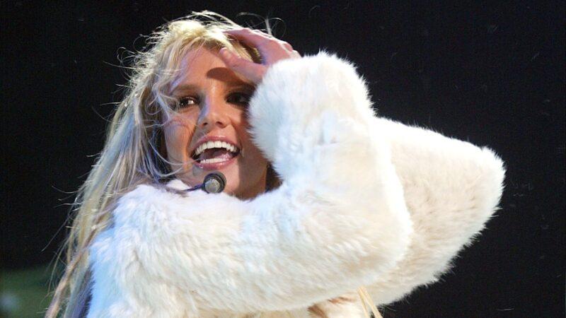 Britney Spears wears a white fuzzy jacket onstage