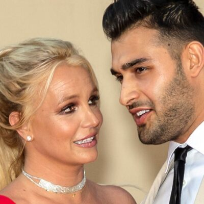Britney Spears wears a red dress and stands with Sam Asghari, in a beige suit, on the red carpet