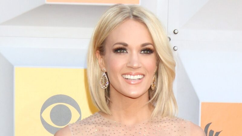 Carrie Underwood wears a sheer gold dress on the CMA red carpet
