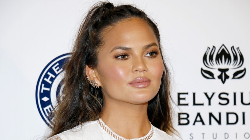 Chrissy Teigen wears a white dress on the red carpet and poses in front of a white background