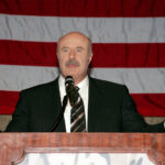 Dr. Phil with his arms out, standing at a podium, in front of an American Flag