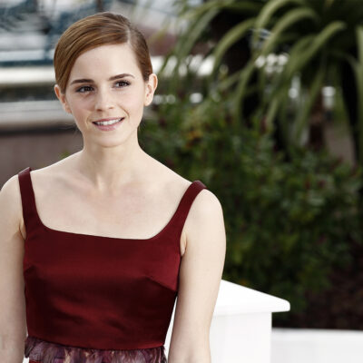 Emma Watson smiling in a red dress, sitting on a white chair