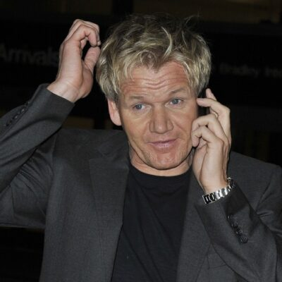 Gordon Ramsay talks on the phone while wearing a dark suit jacket at LAX