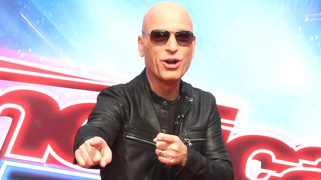 Howie Mandel wears a black leather jacket and points on the red carpet