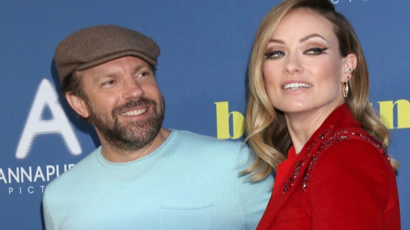 Jason Sudeikis wears a blue shirt and stands with Olivia Wilde, in a red suit, on the red carpet