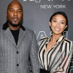 Jeezy, in a gray suit, poses with Jeannie Mai, in a stripped blouse, on the red carpet