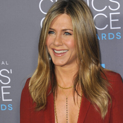 Jennifer Aniston smiling in a red top.