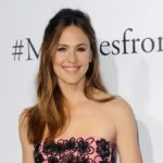 Jennifer Garner wears a pink and black dress against a white background on the red carpet