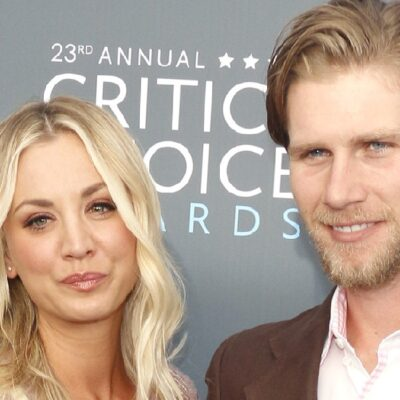 Kaley Cuoco and Karl Cook pose together on the red carpet against a gray background