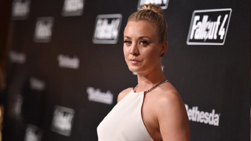 Kaley Cuoco wears a white dress against a black background