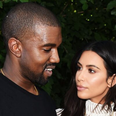 Kanye West, dressed in a black t shirt, looks down as Kim Kardashian, in a white knit dress, looks at him