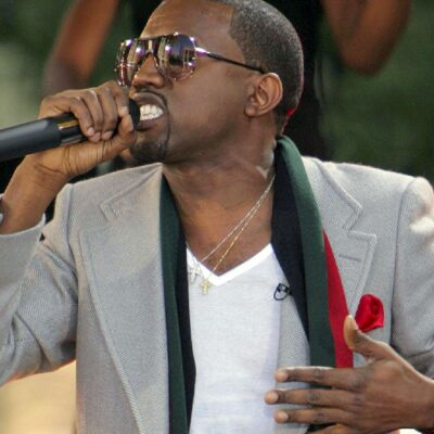 Kanye West wears a gray blazer over a white shirt as he performs onstage