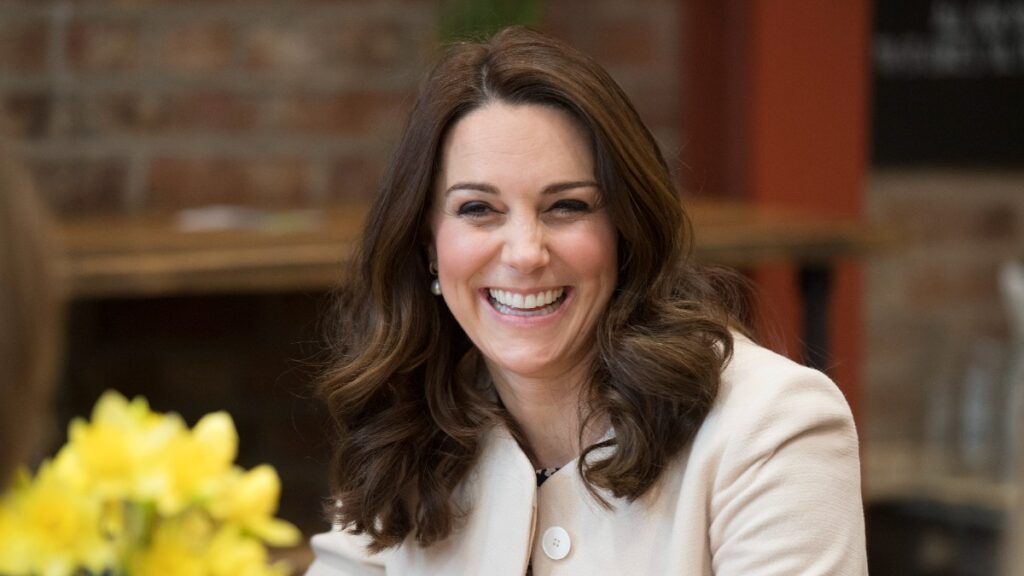 Kate Middleton wears a light colored coat while seated indoors