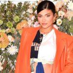 Kylie Jenner wear an orange jacket against a floral background