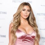 Larsa Pippen wears a pink dress against a white background on the red carpet