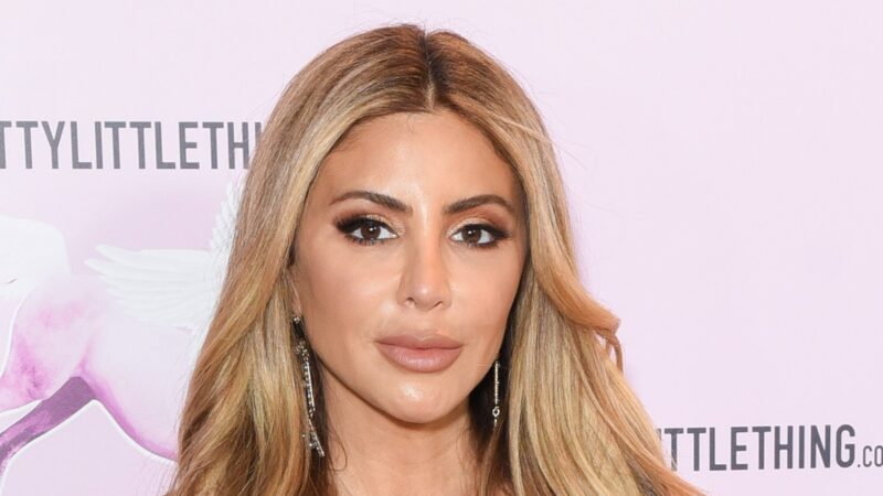 Larsa Pippen wears a strapless black dress against a pale pink background