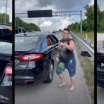 A Lyft driver wearing a black top and shorts stands by her car on the side of a Nashville highway