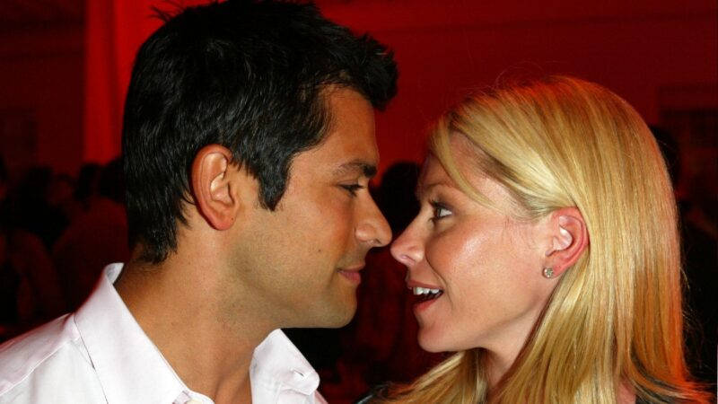 Mark Consuelos, in a white shirt, leans in close to Kelly Ripa