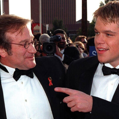 A young Matt Damon on the right, pointing at Robin Williams on the left, together at a red carpet event.