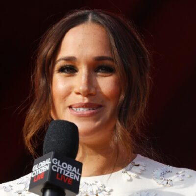 Meghan Markle wears a white dress on stage as she makes remarks