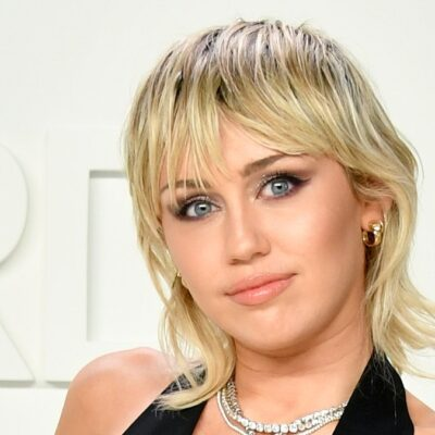 Miley Cyrus wears a black jumpsuit with a plunging neckline against a white background
