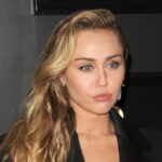 Miley Cyrus wears a black suit against a black background on the red carpet